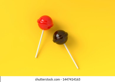 Red and brown lolipop on yellow pastel color background.sweet candy concept