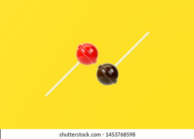 Red and brown lolipop on yellow pastel background.sweet candy concept