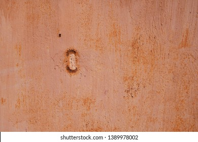 Red brown painted grunge metal garage wall background with hole. Copy space