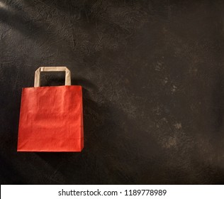 Red and brown paper shopping bag on dark background, with space for your logo or text