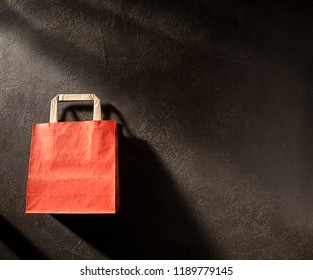 Red and brown paper shopping bag on dark background, with space for your logo or text.