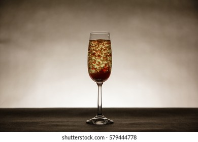 Red bubbles in tall champagne glass