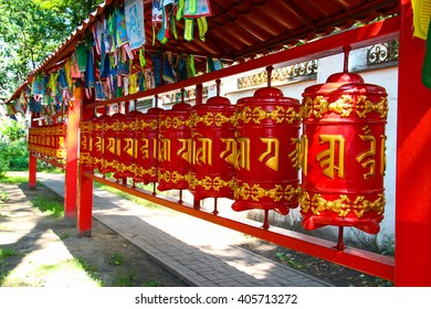 Red buddhist prayer wheels with gold text of the prayers in Sanskrit