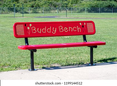 red buddy bench on a school play ground. A bench for a shy or lonely child to sit on to indicate they need a friend or a buddy