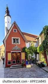 Red building facade and tall tower of church of Holy Spirit in the old town of Tallinn, Estonia