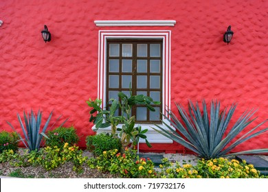 Red building in Mexican Caribbean style with agave