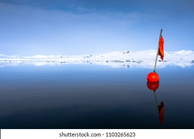 Red buoy floating in the middle of a fjord, Spitsbergen