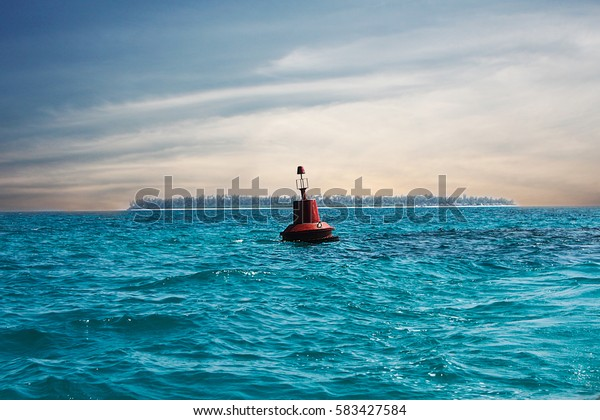 A red buoy floats in the middle to mark the direction and depth for boats