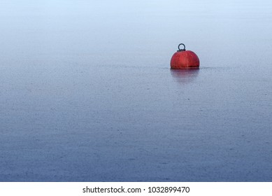 red buoy frozen in ice on the blue water in a lake or the sea, abstract background for winter season and yachting break, metaphor of deadlock, generous copy space, selected focus