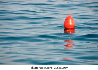 Red buoy on the blue sea. A buoy is a floating device that can have many purposes.
