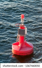 Red Buoy with a Small Solar Panel in the Ocean