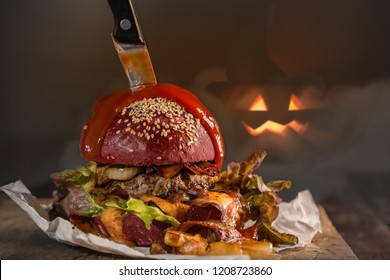Red burger menu for Halloween party. Ketchup as blood on the top and knife. Halloween pumpkin at background