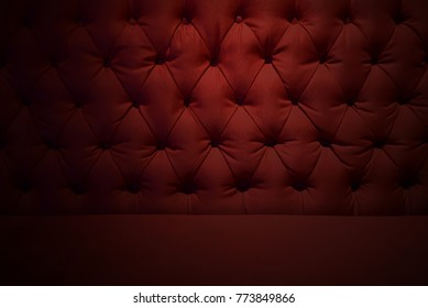 Red burgundy velvet texture or background and soft tufted fabric furniture diamond pattern decoration with buttons.