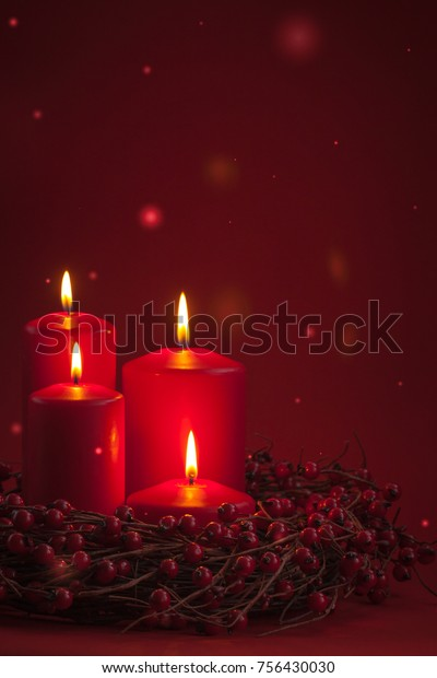 Red burning Advent Christmas candles with the berries wreath on a red background. Toned.