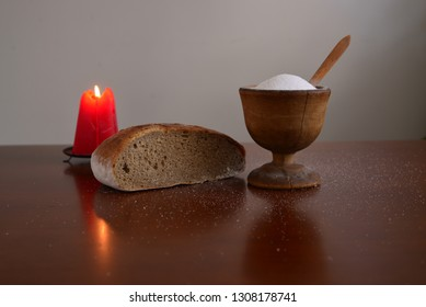 Red burning candle with bread and salt still life.