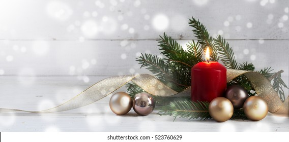 Red burning candle with christmas decoration, fir tree, baubles and ribbon, in front of a white  wooden wall with bokeh lights and generous copy space, panorama, selective focus, narrow depth of field