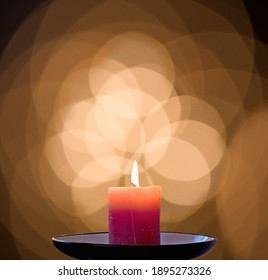 red burning candle with circular background