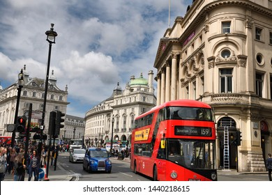 Red bus and blue taxi at Coventry and Haymarket streets with the Quadrant and the London Pavilion at Piccadilly Circus Westminster London, England - June 8, 2019