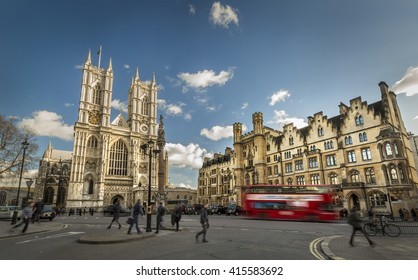 Red bus and people are moving next to the Westminster Abbey (The Collegiate Church of St Peter at Westminster) - Gothic church in City of Westminster, London. Place of coronation of English monarchs
