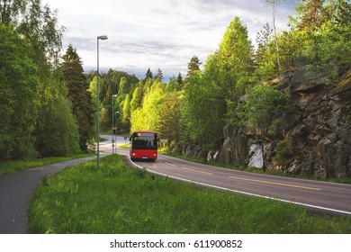 Red bus in the road of Norway and green forest at sides