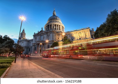 red buses passing Saint Paul's Cathedral in evening