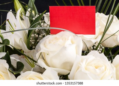 Red business card in a bouquet of white roses. Copy space