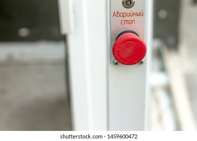"red button on the metal structure and the words ""emergency stop"""