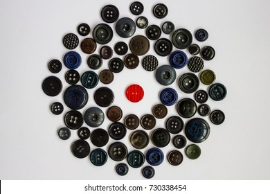 The red button is surrounded by other buttons of dark color. Distinction, individuality, bright personality among the gray world. Rejection, isolation, rejection by others. Protest against ordinary.