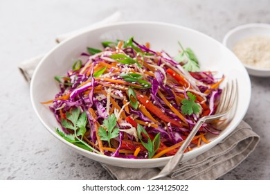 red cabbage, carrot and bell pepper cole slow salad, healthy vegan salad in white bowl, selective focus