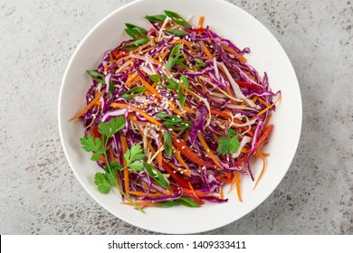 red cabbage, carrot and bell pepper cole slaw salad, healthy vegan salad in white bowl, top view, copy space
