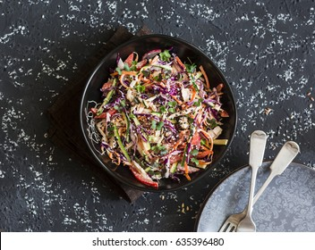 Red cabbage coleslaw with poached chicken. Healthy food concept. Salad with red cabbage, carrot, pepper, radish and boiled chicken, on a dark background, top view