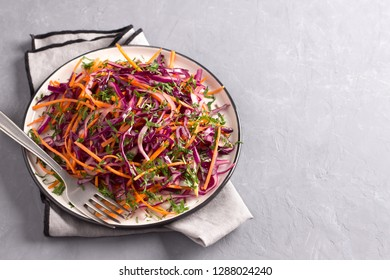 Red cabbage coleslaw salad with cumin and mustard sauce on gray background, top view, horizontal, free space