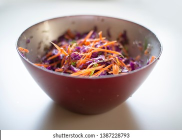 red cabbage salad with carrot and celery chopped thinly, sliced, in a red bowl, dish. isolated on white