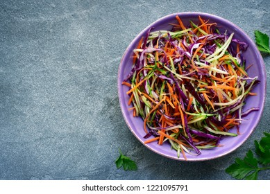 Red cabbage salad cole slaw with carrot and cucumber in a bowl on a dark grey slate, stone or concrete background.Top view.