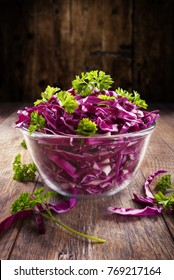Red cabbage salad with green parsley with wood background