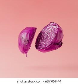 Red cabbage sliced on pastel pink background. Minimal fruit concept.