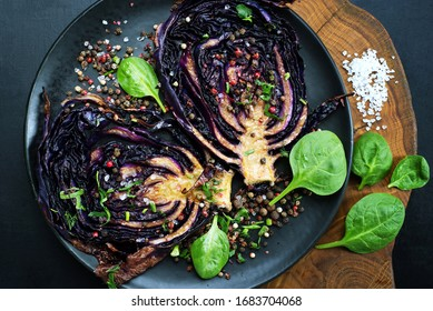 Red cabbage steaks on a black plate on a dark background. Vegetarian, vegan dish