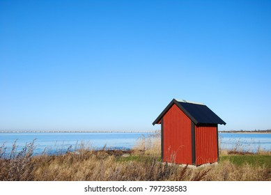 Red cabin by the coast with the swedish Oland Bridge in the background