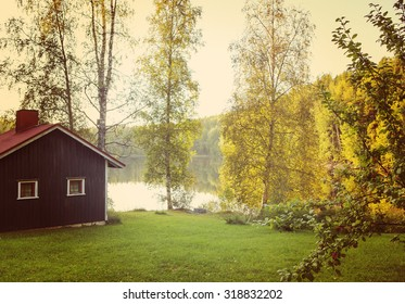 A red cabin or sauna by the lake.  Image taken during early autumn and sunset. An apple tree is in the right side and focus point is on the red cabin. Image has a vintage effect applied.