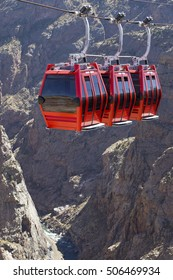 Red cable car going over deep canyon