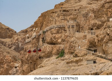 Red cable cars in front of the Monastery of the Qurantul on the  Palestinian Mount of Temptation where Jesus resisted the temptations of Satan after fasting for 40 days in the desert.