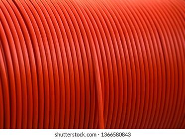 red cable for the transmission of camera data rolled up on a cable drum many hundreds of meters long