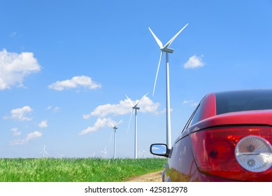 Red cabriolet car and wind turbines generating electricity.