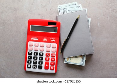 Red calculator and notepad with banknotes on grey background