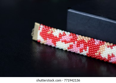 Red camouflage seed beads bracelet on a dark background close up