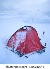 Red camp tent in snowy winter