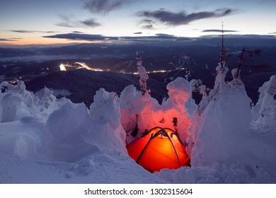 Red camp tent in winter mountains at the night