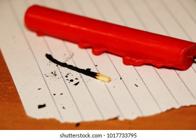 A red candle with burned match on the tattered paper