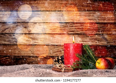 Red candle with christmas decoration and snow in front of wooden wall with bokeh and copy space