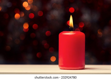 Red candle with fire against defocused lights